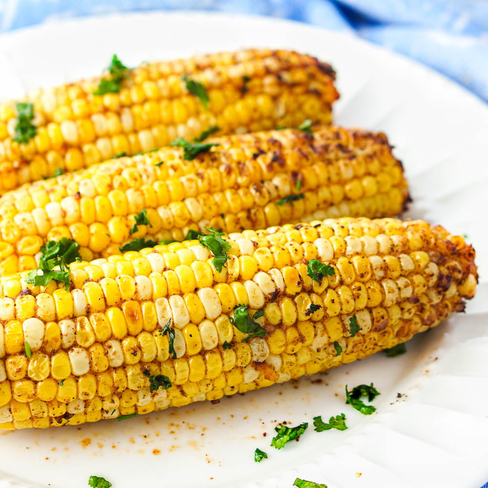 close up of spicy air fryer corn on the cob with cilantro on top
