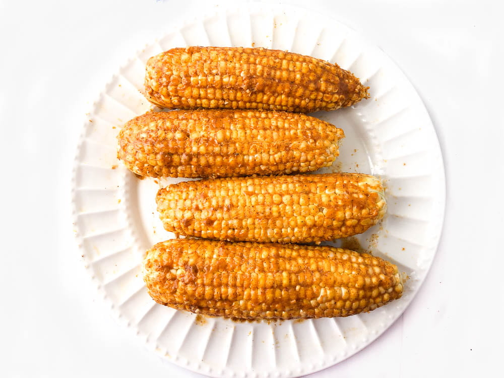 white plate with 4 ears of corn with spicy butter ready to cook