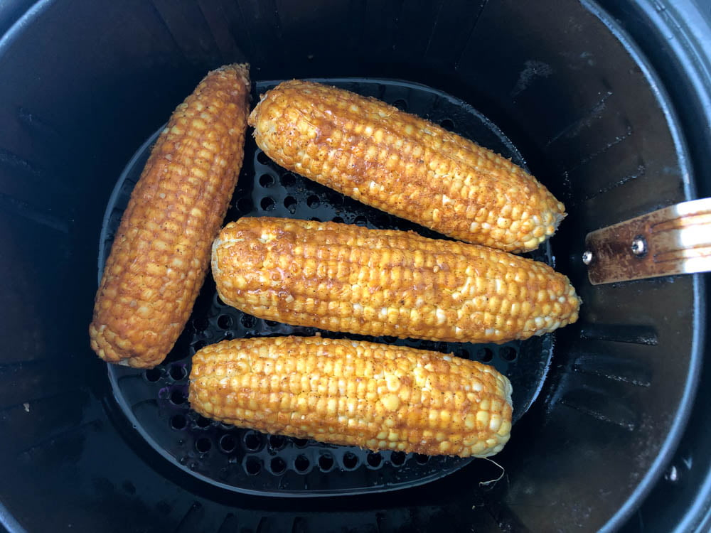 spicy raw corn on the cob in an air fryer basket