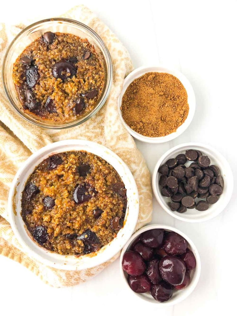 aerial view of 2 cups of baked quinoa breakfast with dishes of chocolate chips and cherries