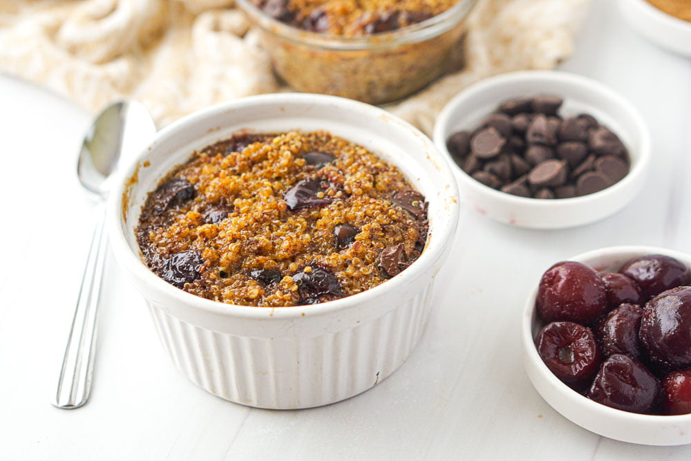 closeup of white ramekin right out of the oven with chocolate chips and cherries in the background