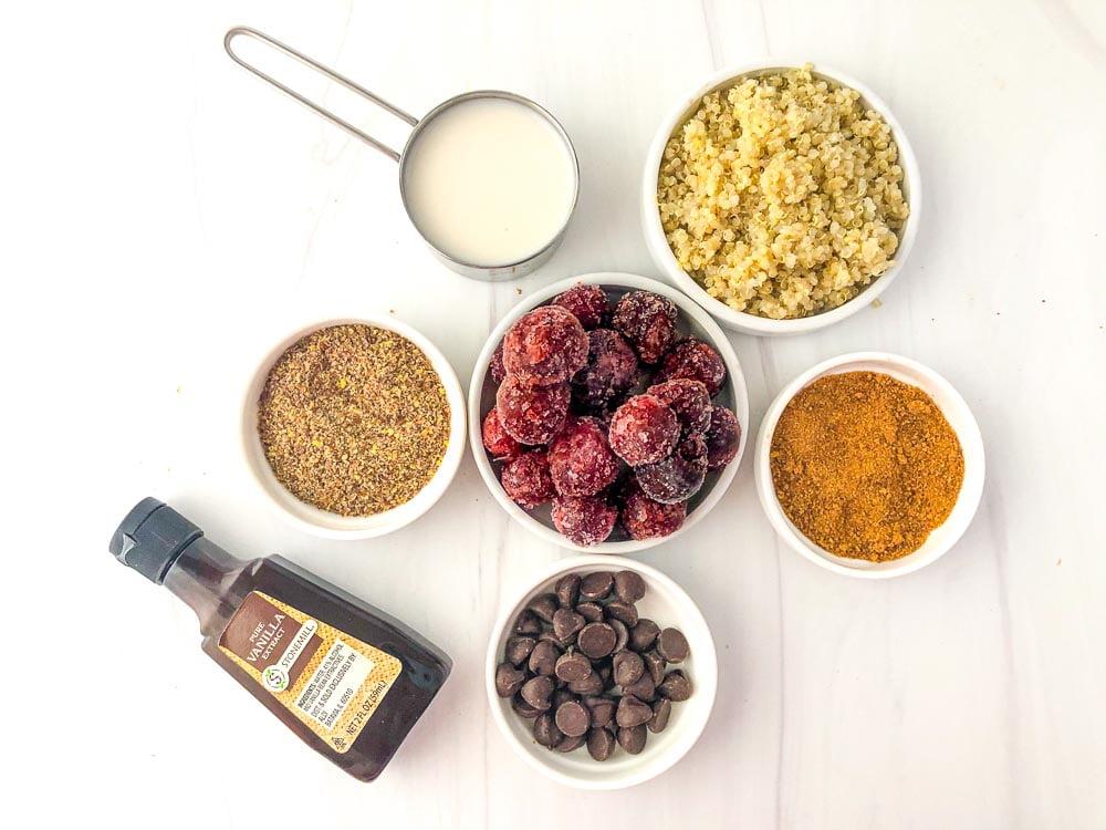 ingredients to make breakfast quinoa - brown sugar, dark chocolate chips, frozen cherries, almond milk, flaxseed, cooked quinoa, vanilla extract
