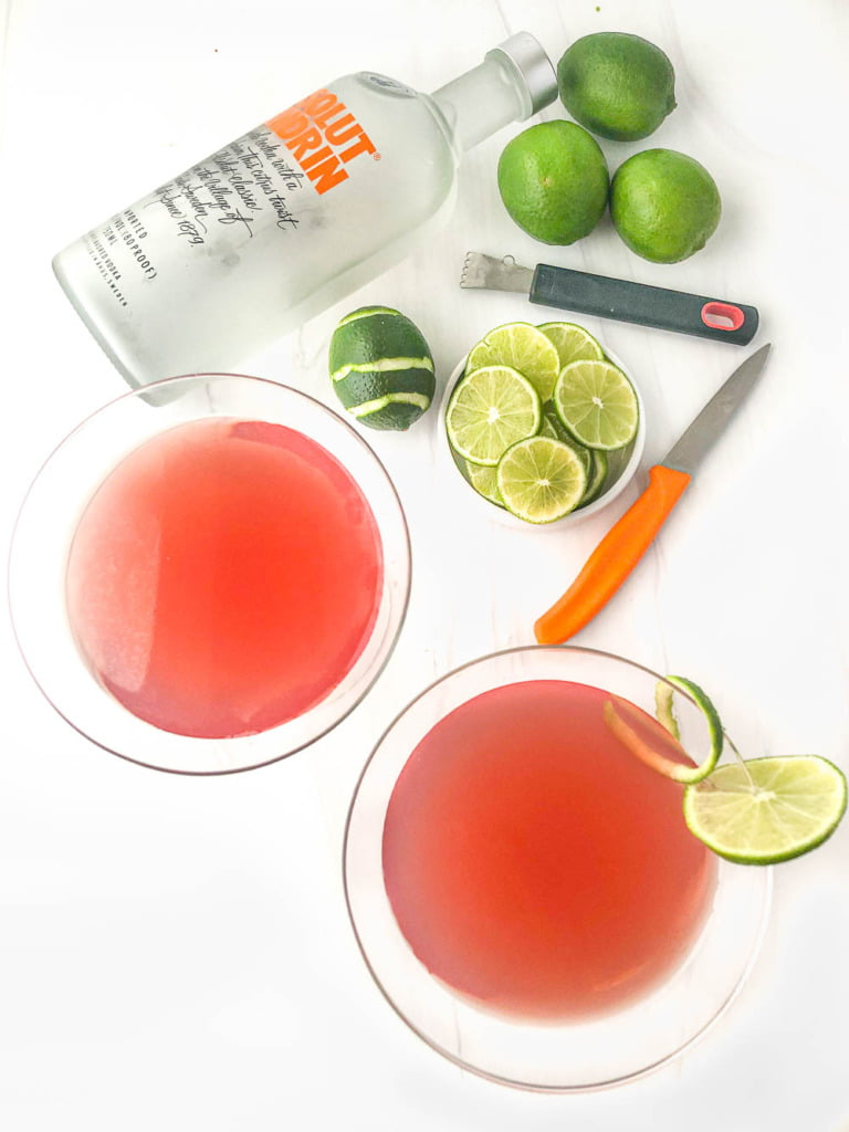 aerial view of a bottle of Absolut Mandarin, knife, lime slices and 2 cosmo martinis