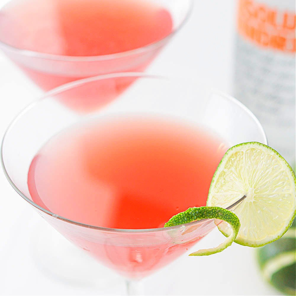 closeup of a martini glass with a keto cosmopolitan drink and slice of lime