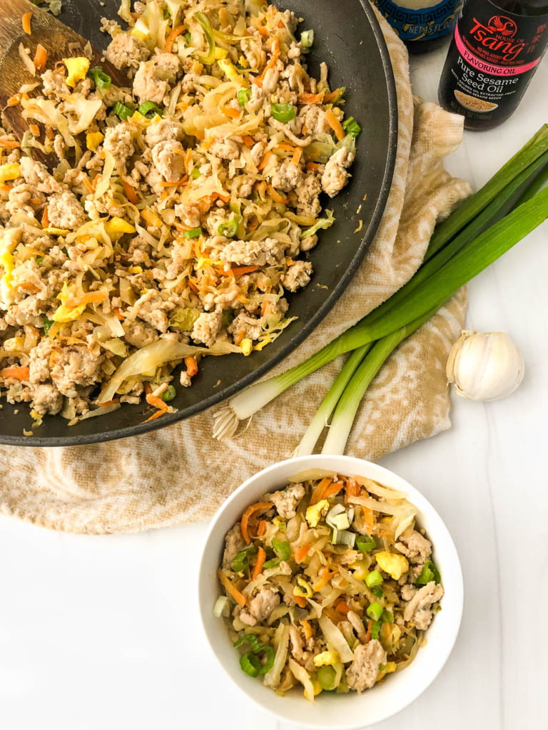aerial view of a bowl and pan with ground chicken egg roll stir fry and scallions and garlic