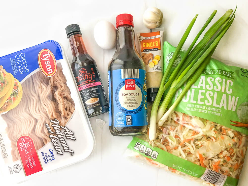 ingredients for recipe: ground chicken, sesame oil, soy sauce, ginger paste, green onions, coleslaw and garlic and eggs