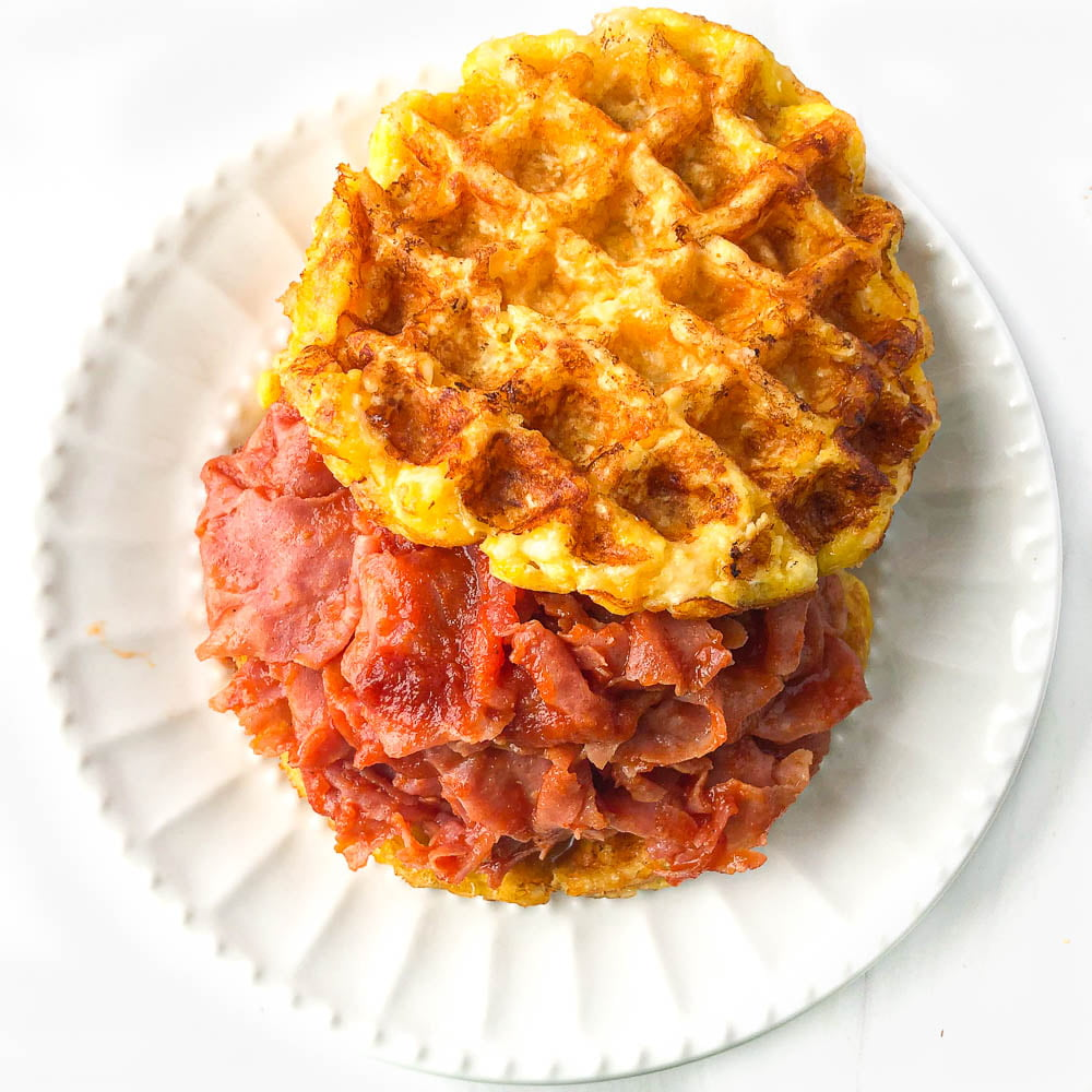 white plate with a low carb chipped ham bbq sandwich using keto cheese waffle buns