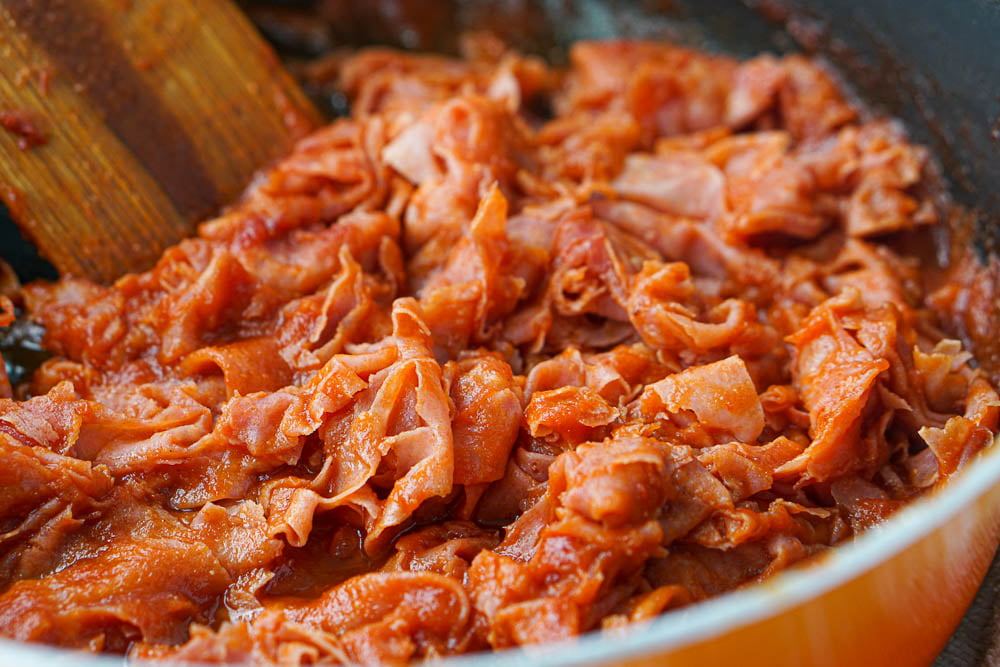 closeup of a pan of ham barbecue and a wooden spoon