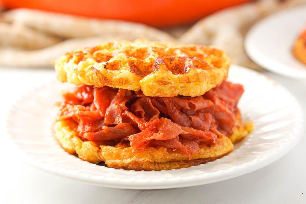 closeup of a waffle ham bbq sandwich on white plate