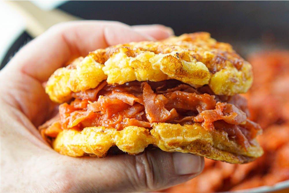 hand holding keto ham bbq sandwich with waffle bun
