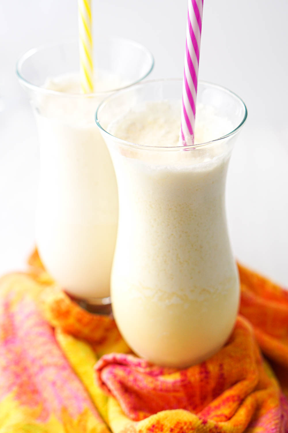 2 tall glass with froze sugar free pina coladas with colorful straws