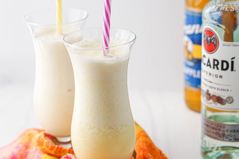 two frozen coconut drinks with a bottle of Bacardi and pineapple syrup