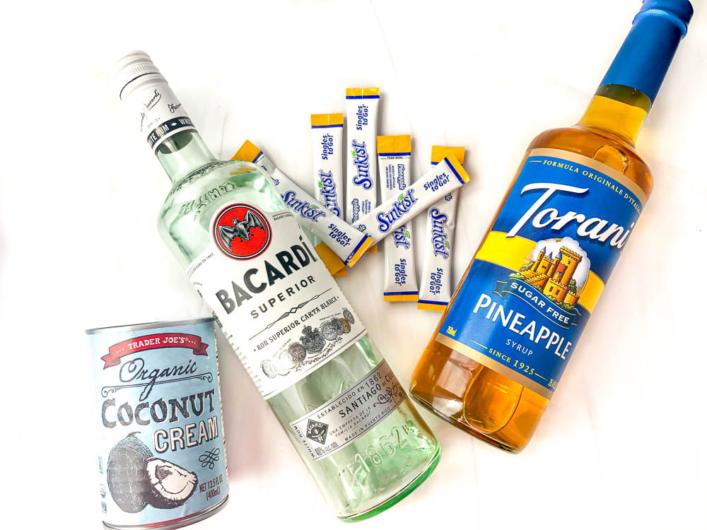 ingredients to make keto frozen drink -  Bacaradi rum, can of coconut cream, Sunkist pineapple drink mix, Torani sugar free pineapple syrup