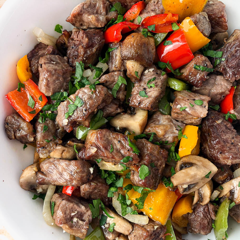 closeup of air fryer steak tips with pepper, onions and mushrooms and parsley scattered on top