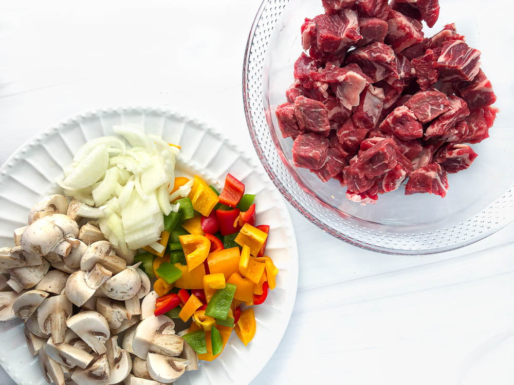 white plate with raw peppers, onions and mushrooms and a glass bowl of raw steak cubes