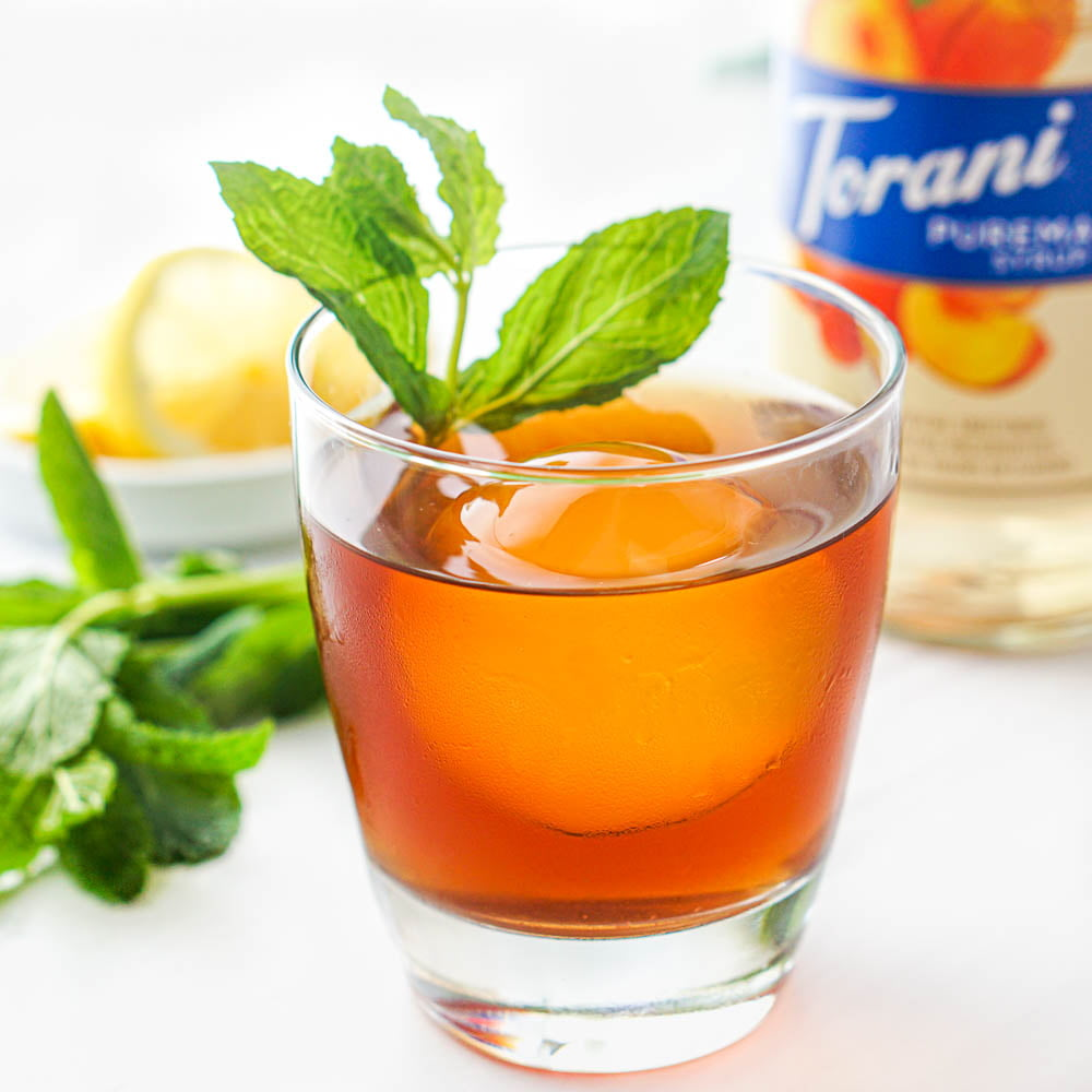 closeup of a keto bourbon peach smash drink with a sprigs of fresh mint