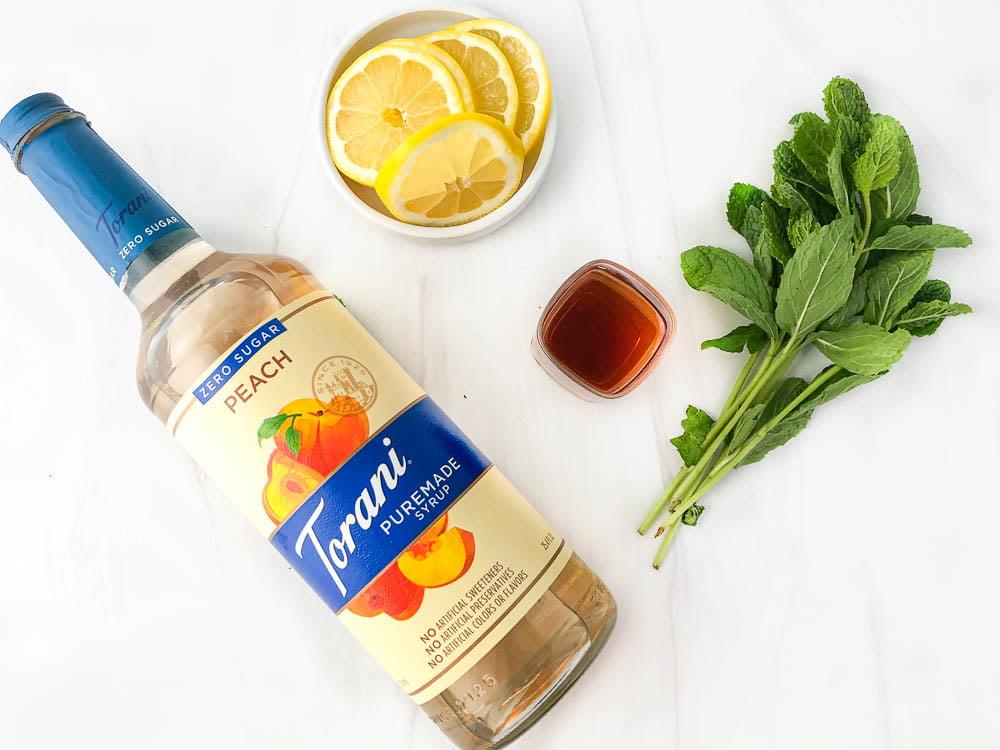 ingredients to make sugar free bourbon smash drink: Torani puremade zero sugar peach syrup, lemon slices, sprigs of mint and shot glass of bourbon