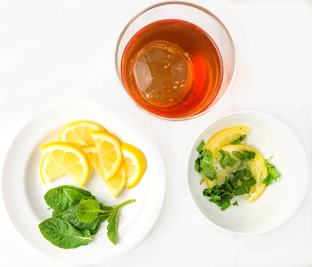 highball glass with peach smash drink, white plate and bowl with muddles lemons and mint