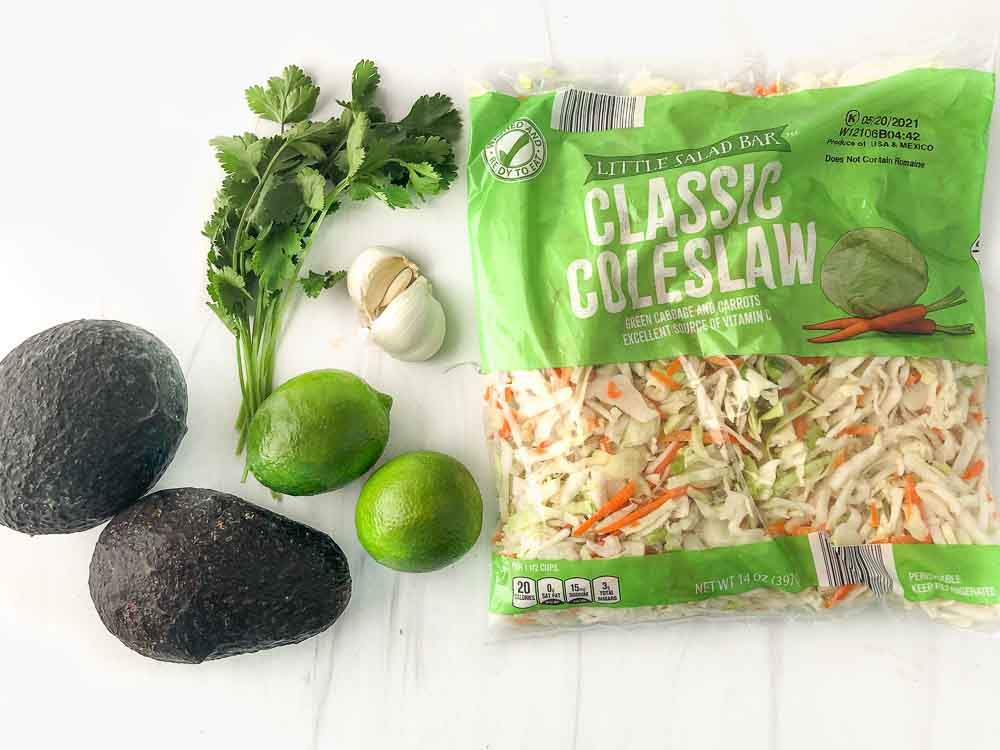 ingredients to make recipes: bag of coleslaw mix, limes, avocados, garlic and fresh cilantro