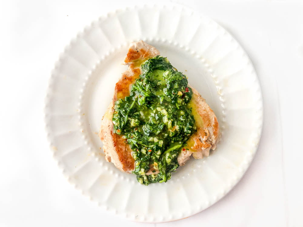 a piece of tuna steak on a white plate with cilantro green sauce on top