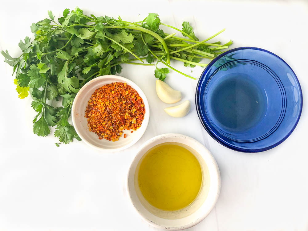ingredients to make chimichurri - cilantro leaves, garlic, vinegar, olive oil and red pepper flakes