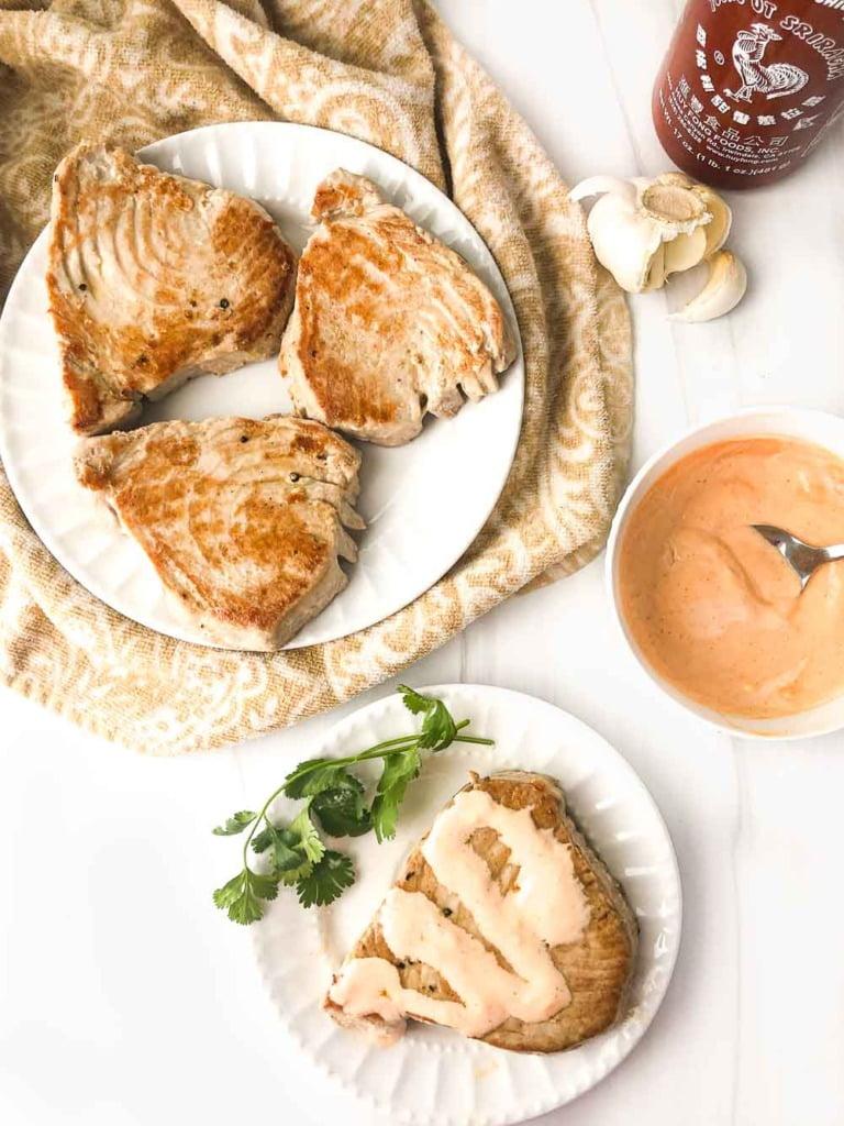 white plates with fresh tuna steaks and creamy sriracha mayo