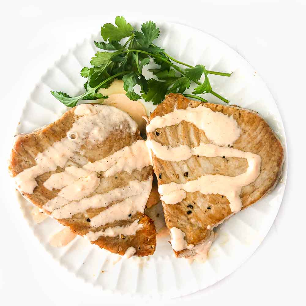 white plate with tuna steaks with keto creamy sriracha sauce and parsley sprigs