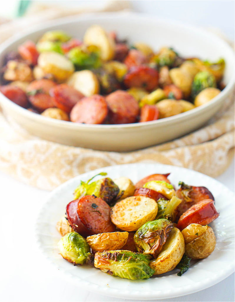 closeup of white plate with Brussels and kielbasa dinner with big bowl in background