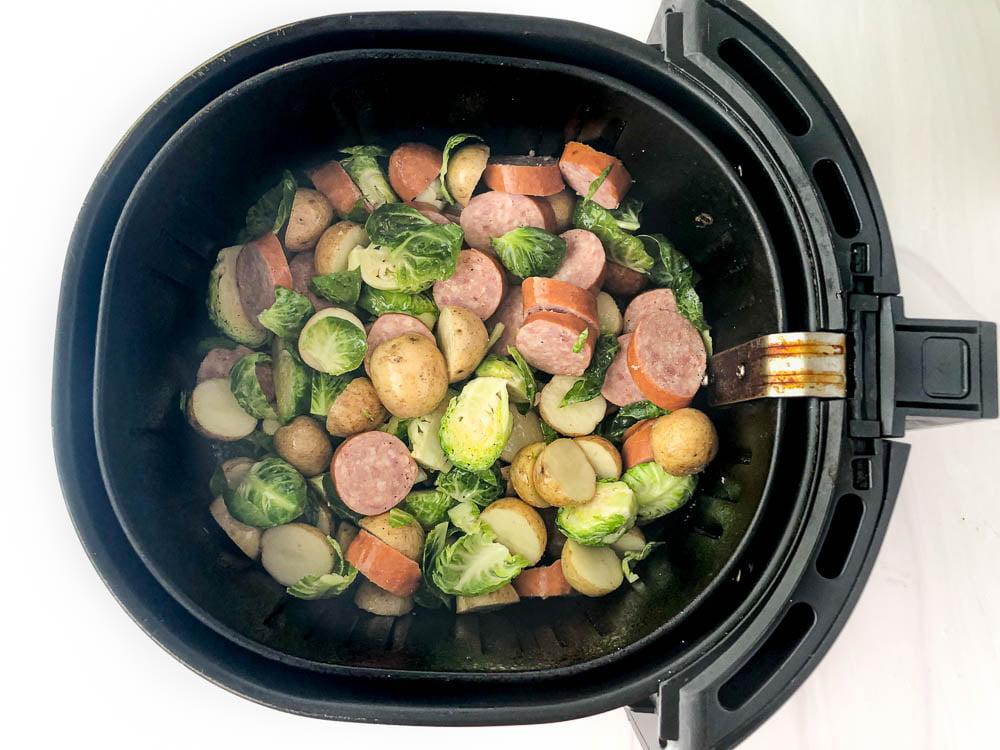 black air fryer basket with raw ingredients