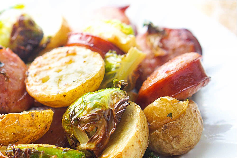 closeup of roasted sprouts and potatoes and kielbasa slices