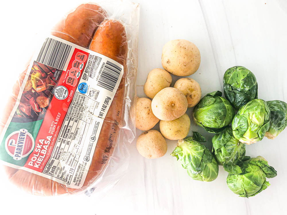 recipe ingredients of kielbasa, raw potatoes and raw Brussels sprouts