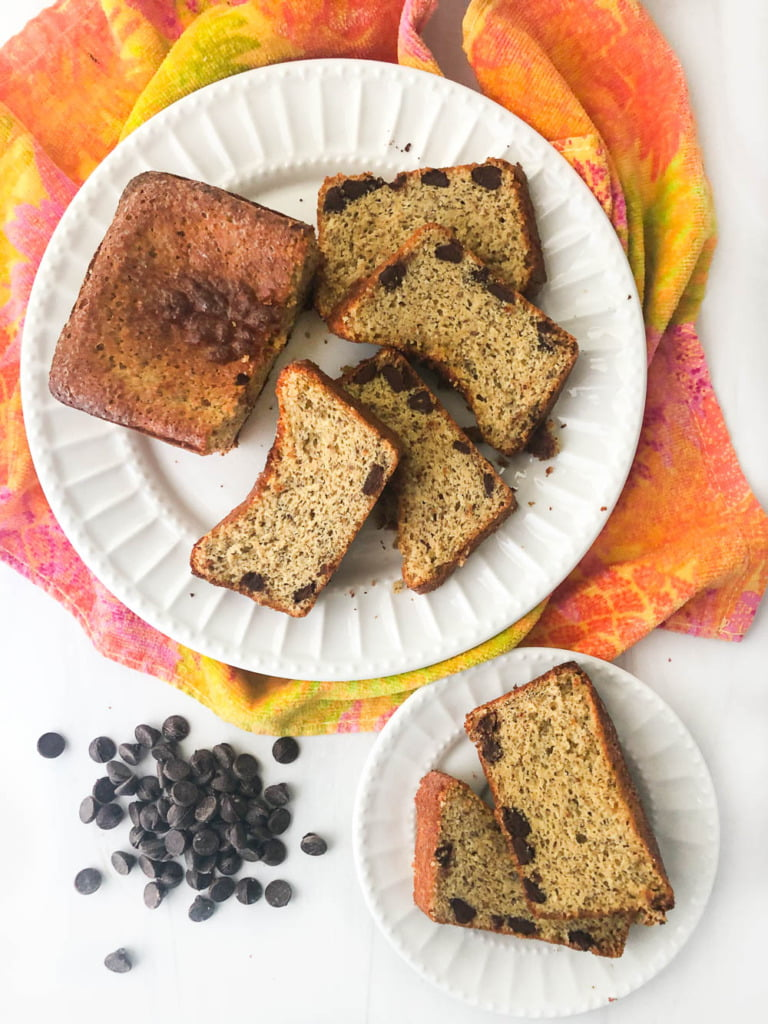 slices of keto chocolate chip bread on white plates with colorful orange and yellow tea towel and scattered sugar free chocolate chips
