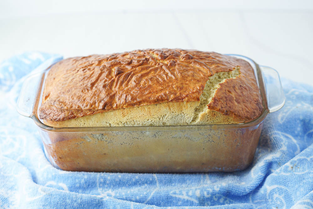 big loaf of keto banana bread in glass dish and light blue towel underneath