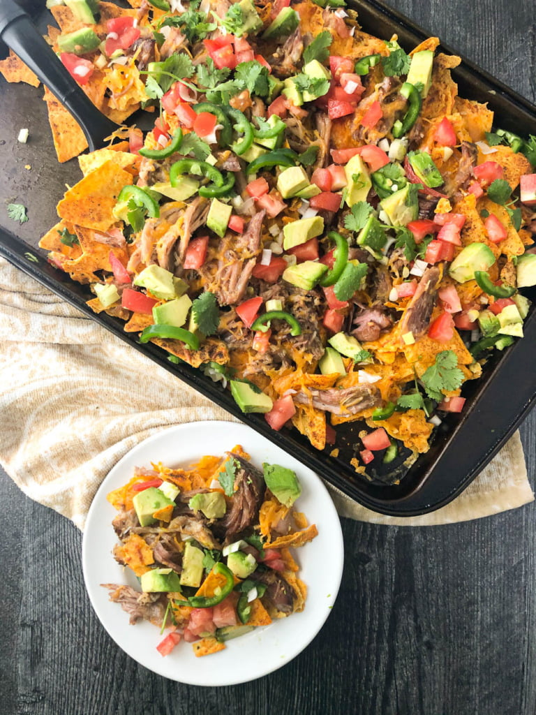aerial view of a cookie sheet and white plate with low carb nachos topped with pork, tomatoes cheese, avocados, etc