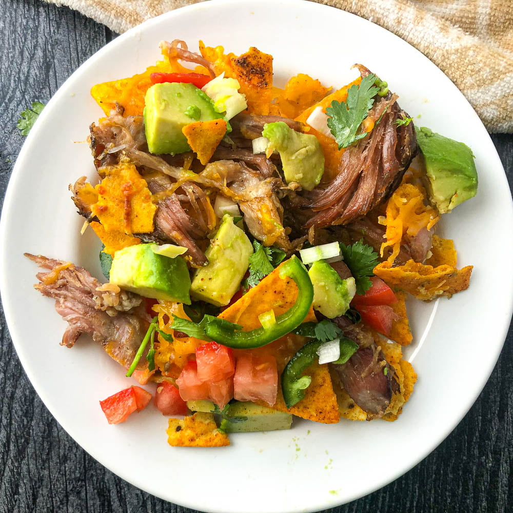 white plate with pulled pork keto nachos with avocados, jalapenos, tomatoes and more