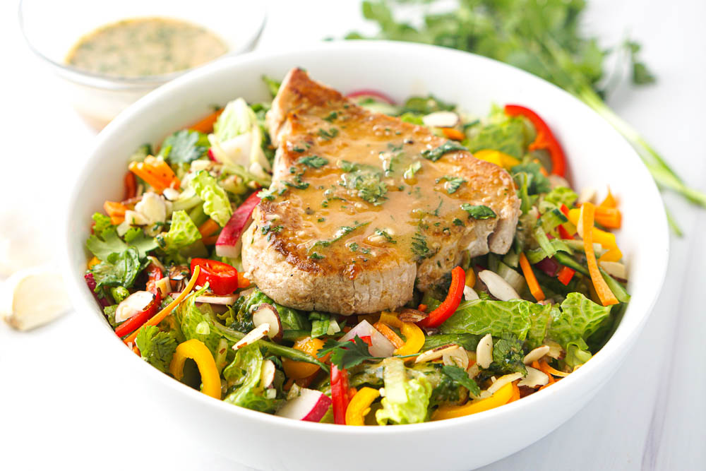 white bowl with colorful salad and topped with a tuna steak and Asian salad dressing