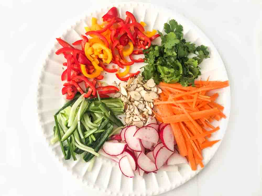 white plate with cutup colorful vegetables for Asian salad