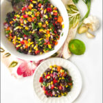 white bowl and plate with Mexican bean salad and text