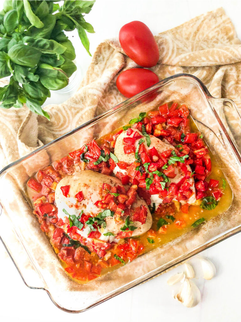 baking dish with chicken caprese and a big bunch of fresh basil and fresh tomatoes