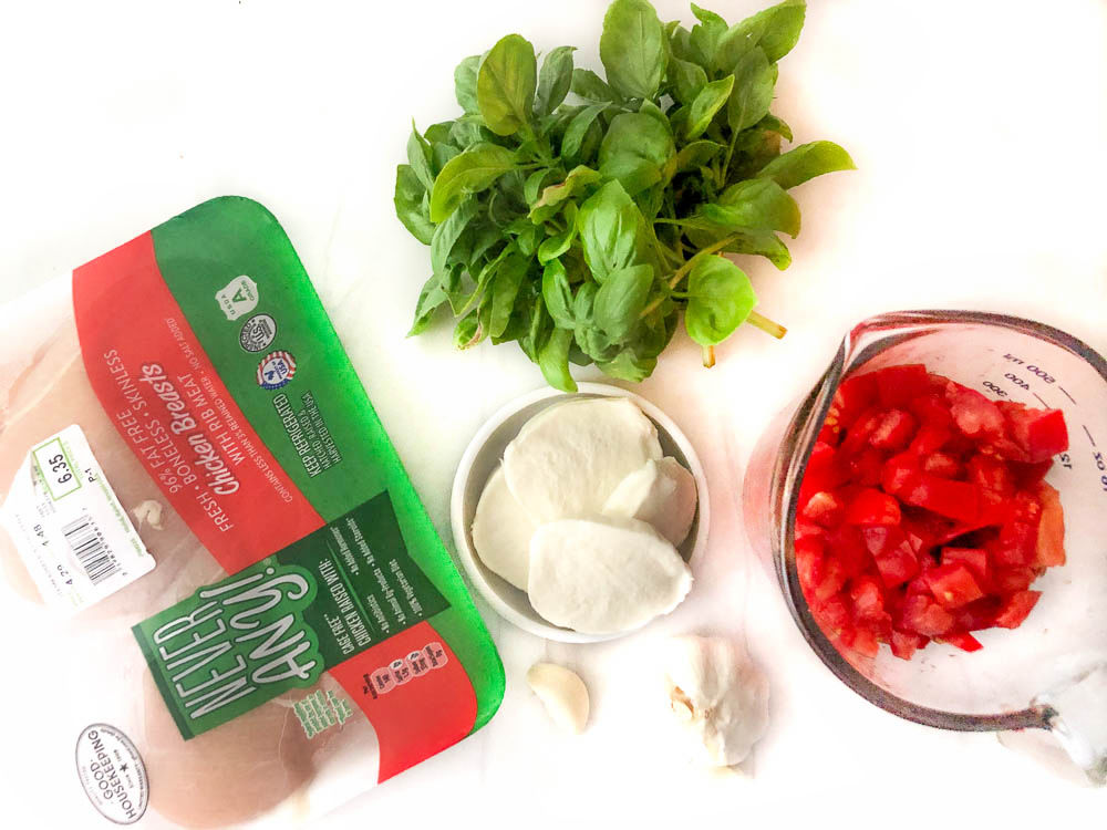 ingredients for baked chicken - chicken breasts, fresh basil, chopped fresh tomatoes, garlic and fresh mozzarella cheese