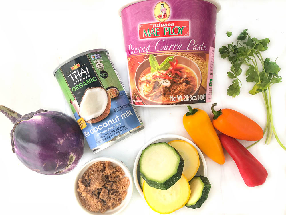 ingredients to make vegetable curry - eggplant zucchini, peppers, cilantro, Mae Ploy curry paste, can of coconut milk and brown sugar
