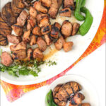 white platter with grilled pork kebabs and text