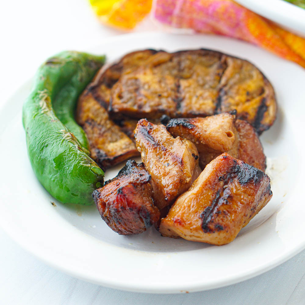 white plate with grilled pork kebabs and grilled veggies