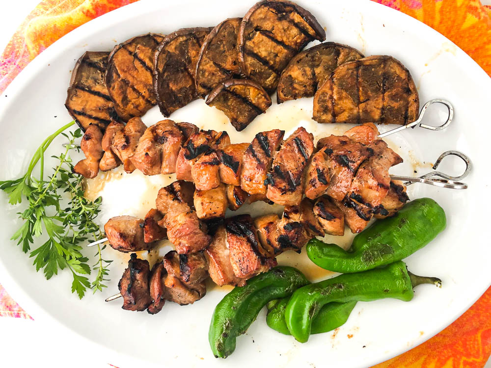 white platter with grilled pork kebabs, eggplant and peppers with fresh herbs
