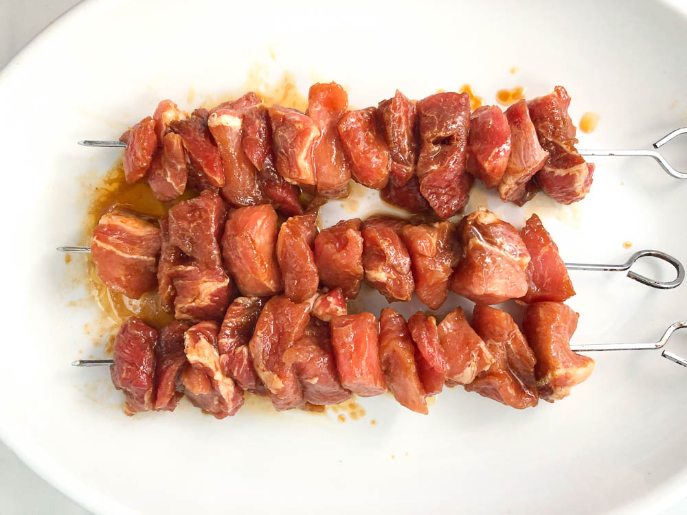 raw marinated pork pieces on skewers