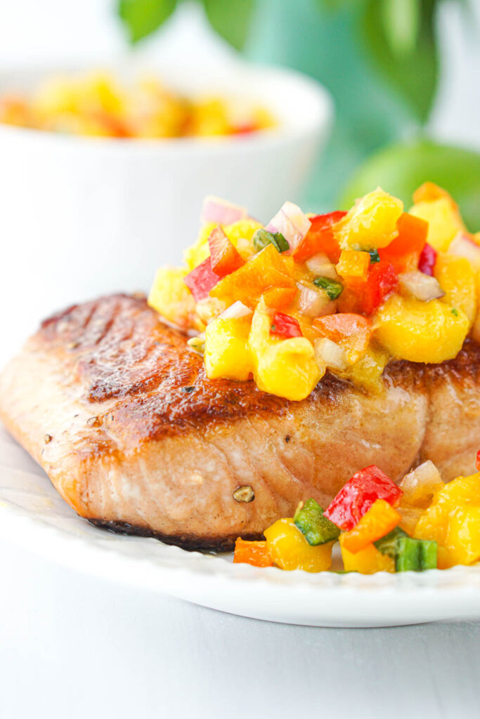 closeup of a piece of salmon topped with chopped mangoes and peppers salsa