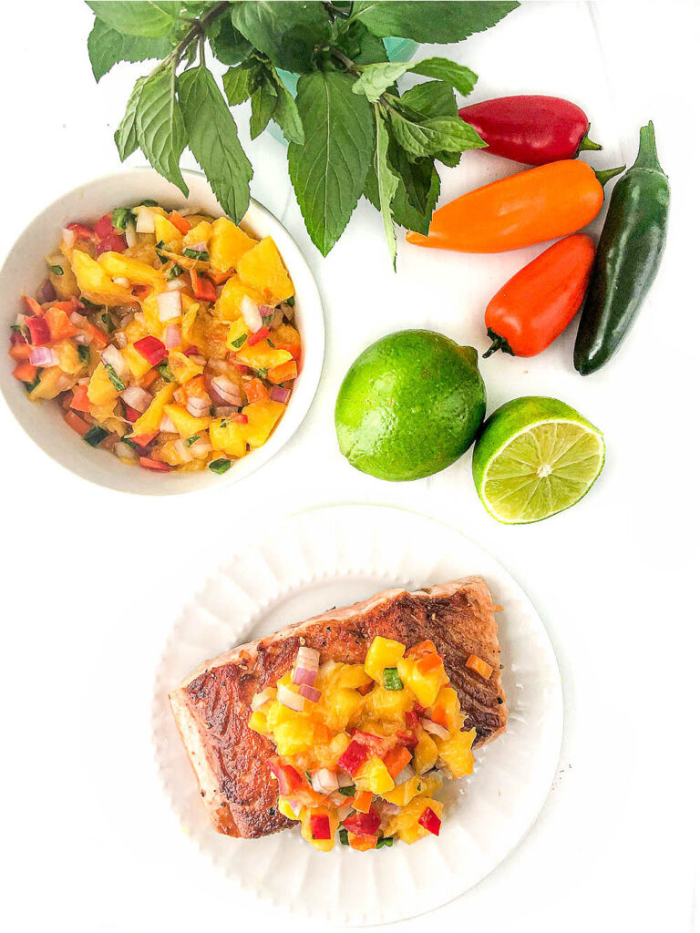 white plate with salmon topped with fruit salsa and fresh limes, peppers and mint