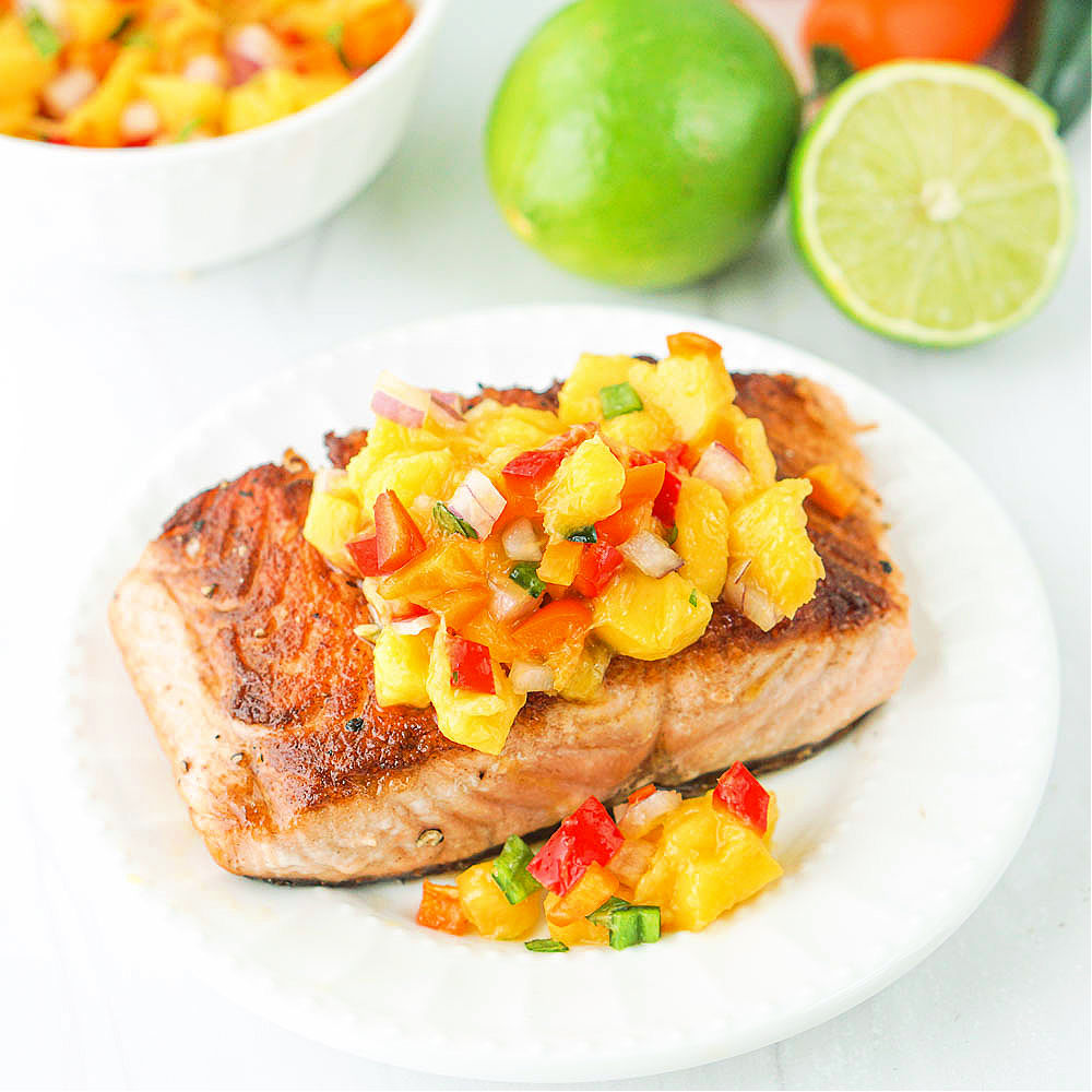 white plate with a piece of salmon topped with spicy mango salsa
