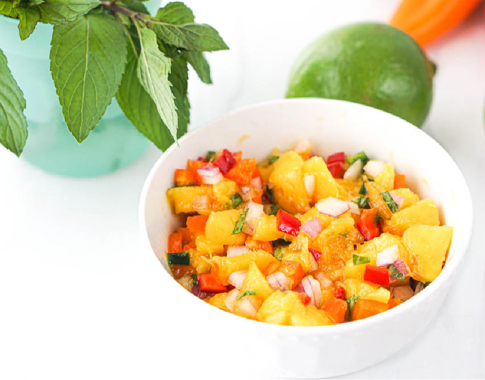 bowl of colorful fruit salsa and fresh mint in the background