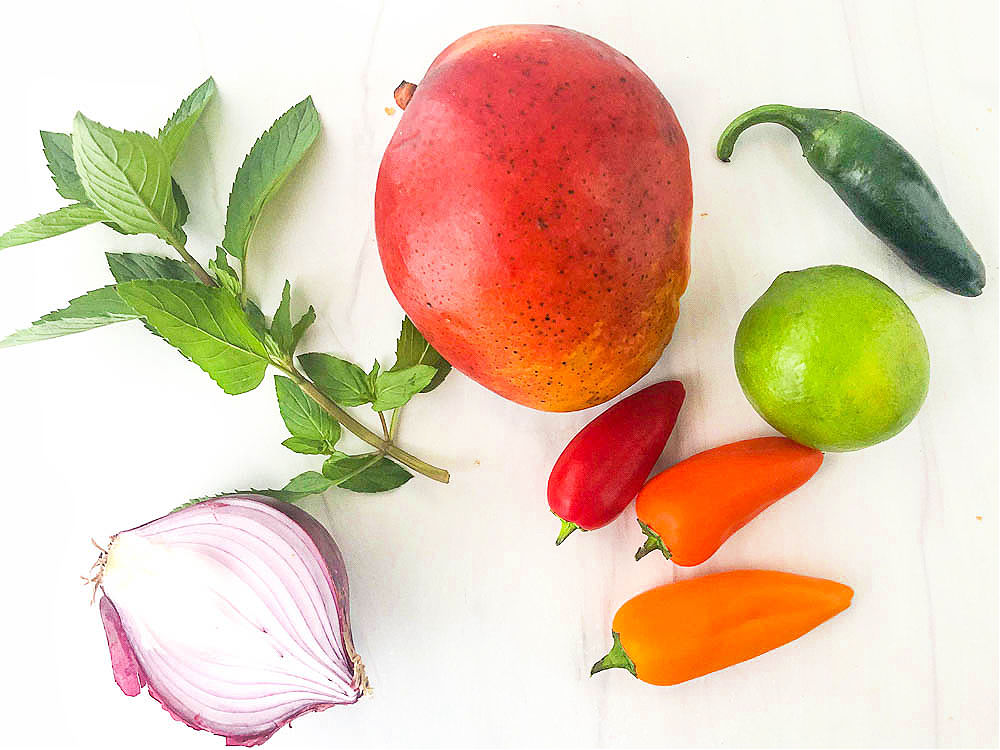 ingredients for mango salsa - red onion, fresh mint, mango, jalapeno, lime and bell peppers